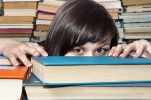 girl hiding behind books